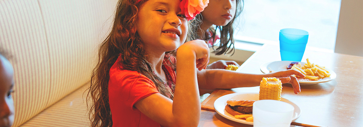 little girl smiles while enjoying her camp kids lunch