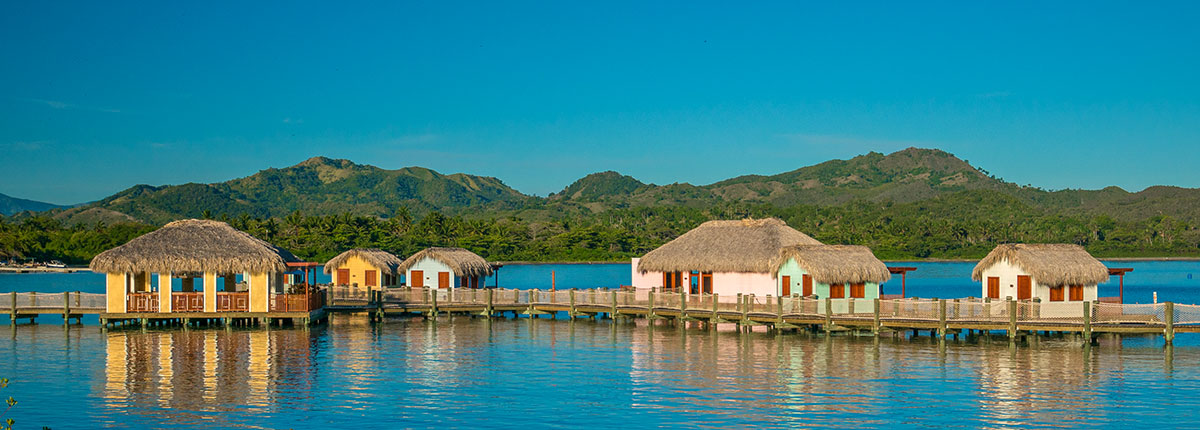 scenic view of tiki huts on the water in Amber Cove.