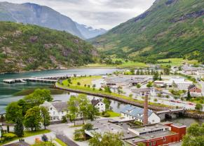 a small town surrounded by a fjord, mountains and lush trees